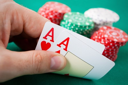 Poker hand with two aces. Some casino chips in the background over a green gaming table. photo