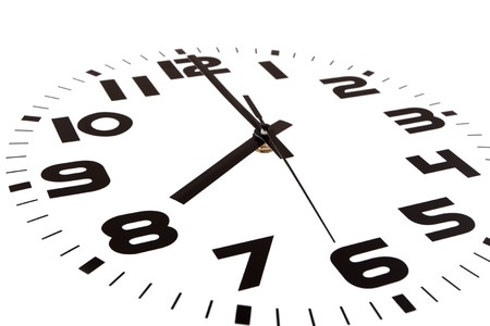 Clock isolated on white marking the eight oclock hour. The main focus is in the hour hand. Stock Photo