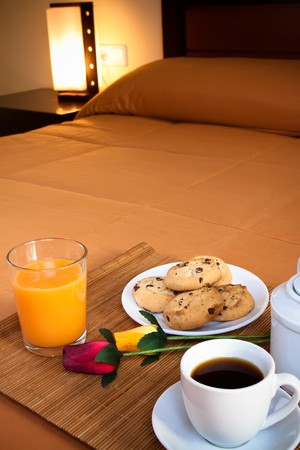 predominant: Coffee, cookies, orange juice and a pair of roses over the bed for a romantic breakfast in an orange predominant image.