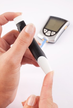 disease control: Diabetic woman pricking her finger for a blood test with a glucometer in the background