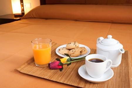 desayuno romantico: Caf�, cookies, jugo de naranja y un par de rosas sobre el lecho de un rom�ntico desayuno en una imagen predominante naranja.