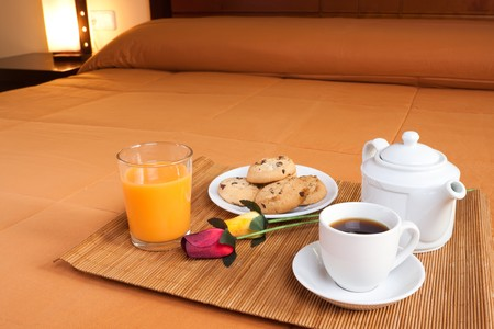 Coffee, cookies, orange juice and a pair of roses over the bed for a romantic breakfast in an orange predominant image. photo