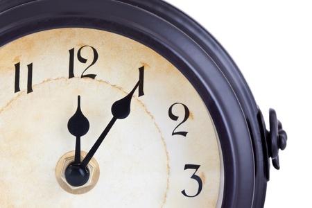 Vintage clock showing five past twelve against a white background