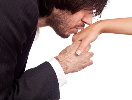 Businessman kissing his womans hand isolated against a white background