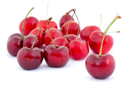 Isolated cherries against a white background with a soft shadow.