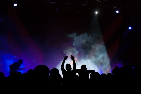 young musician: Live and powerful concert. Dark shot aiming the stage and the silhouettes of the public. The lights are delivered overexposed. Stock Photo