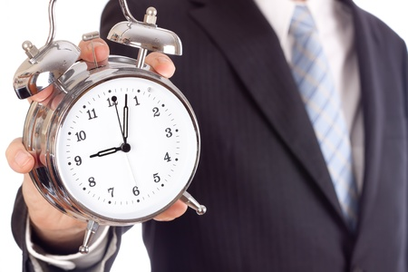 Businessman showing an alarm clock, aiming four past nine. Stock Photo