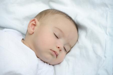 Baby sleeping on white sheet