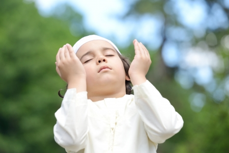 A little Arabic boy praying outdoor in nature 스톡 콘텐츠