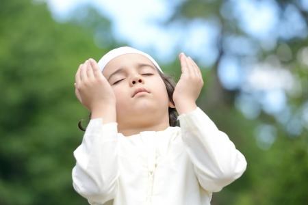 islamic pray: A little Arabic boy praying outdoor in nature Stock Photo