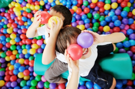 Happy children playing and having fun at kindergarten with colorful balls on eyes 스톡 콘텐츠