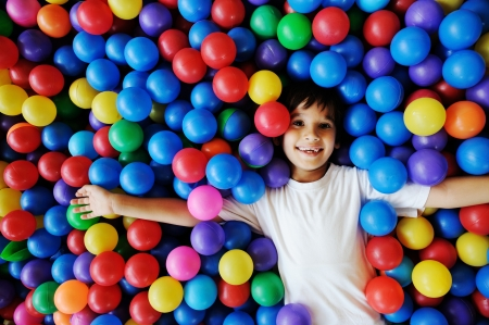 indoors: Little smiling boy playing lying in colorful balls park playground Stock Photo