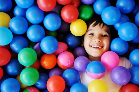 Happy children playing and having fun at kindergarten with colorful balls Standard-Bild