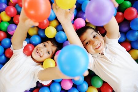 jugar: Ni?os felices jugando juntos y divertirse en el jard?n de infantes con bolas de colores
