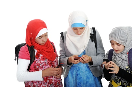 Arabic Muslim girls wearing Islamic clothes using cell phones photo