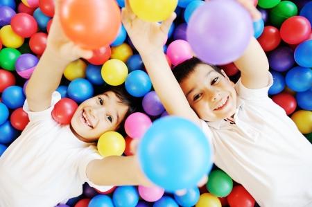Gelukkige kinderen samen spelen en plezier op de kleuterschool met kleurrijke ballen Stockfoto
