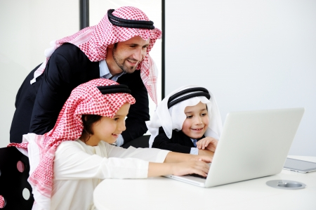 learning arabic: Middle eastern father with sons working on laptop Stock Photo