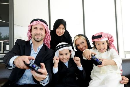 hombre arabe: Feliz familia �rabe jugando en casa con controladores de videojuegos