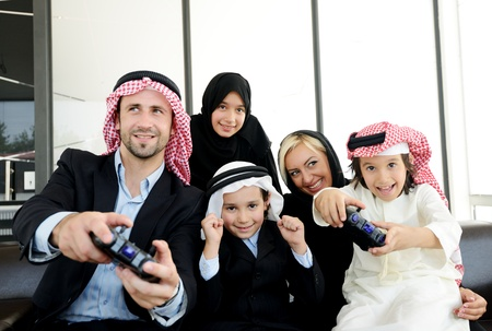 arab girl: Happy Arabic family playing at home with video game controllers
