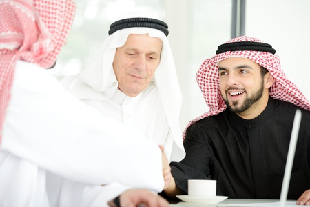Successful Arabic business people shaking hands over a deal