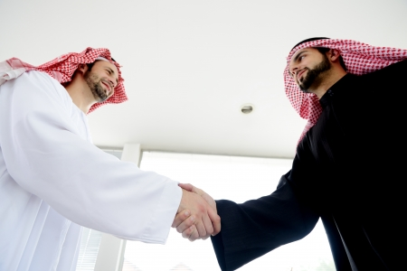 Successful Arabic business people shaking hands over a deal photo