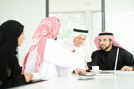 saudi: Successful Arabic business people shaking hands over a deal