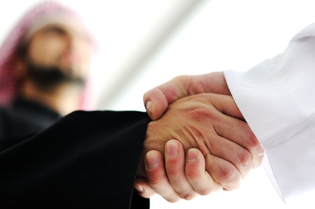 arab: Closeup of business people shaking hands over a deal