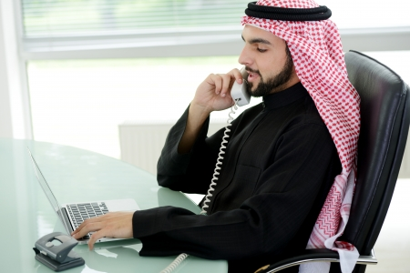 Portrait of a smart arabic business man using laptop and talking  on the phone photo
