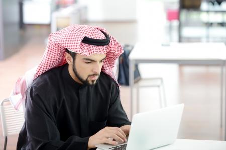 hombre arabe: Moderno empresario �rabe en la oficina de trabajo en la computadora port�til Foto de archivo