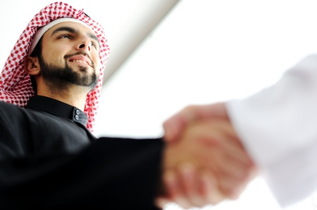 arabic: Successful Arabic business people shaking hands over a deal
