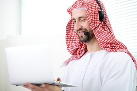 Portrait of a smart arabic business man using laptop and hheadset. Call center. Customer support. Helpdesk. photo