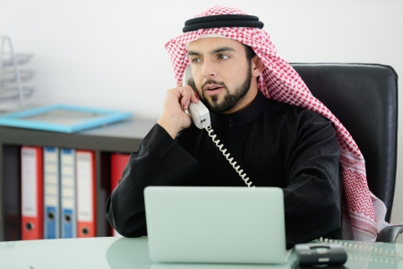 arab adult: Portrait of a smart arabic business man using laptop and talking  on the phone