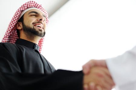 hombre arabe: Hombres de negocios árabes exitosos agitando las manos sobre un acuerdo