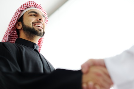 arab man: Successful Arabic business people shaking hands over a deal