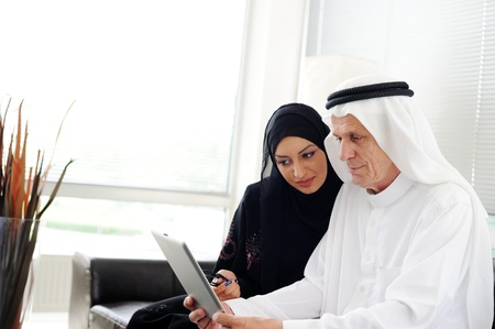 businees: Two couple muslim lookig at tablet on office