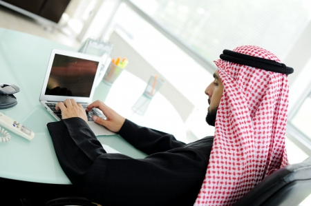 arabic man: Modern arabic businessman on office working on laptop