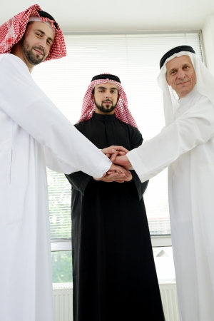 Arabic business team showing unity with their hands together photo