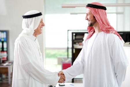headcloth: Successful Arabic business people shaking hands over a deal