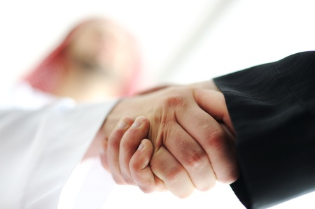 arab business: Successful Arabic business people shaking hands over a deal