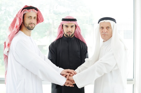 gcc: Arabic business team showing unity with their hands together Stock Photo