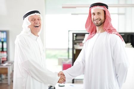 hombre arabe: Hombres de negocios árabes exitosos agitando las manos sobre un acuerdo en la oficina