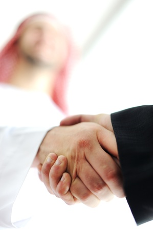 arab adult: Successful Arabic business people shaking hands over a deal