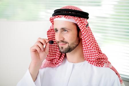 telephone headset: Portrait of a smart arabic business man using headset. Call center. Customer support. Helpdesk.
