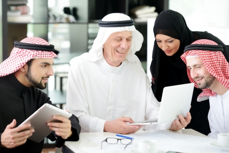gulf: Business arabic people meeting indoor with electronic tablet