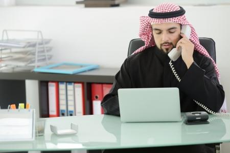 Portrait eines intelligenten arabische Geschäftsmann mit Laptop und spricht am Telefon Standard-Bild - 20136134