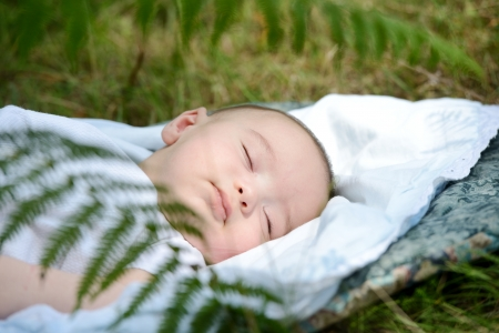 Baby sleeping on green grass outdoor in nature photo