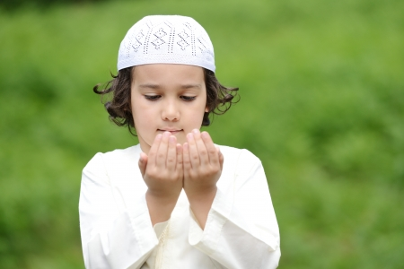 dependent: A little Arabic boy praying outdoor in nature Stock Photo
