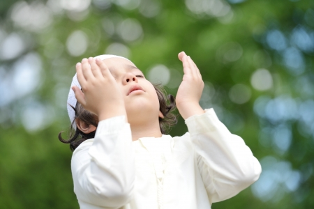 revere: A little Arabic boy praying outdoor in nature Stock Photo