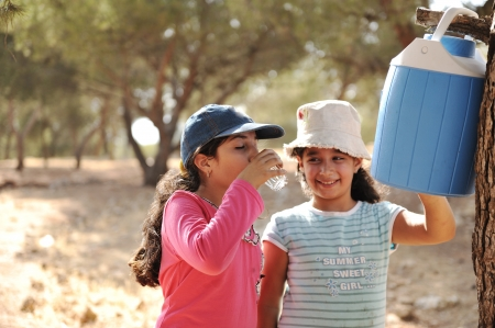 Children having picnic in scout camp in nature, girls drinking water photo