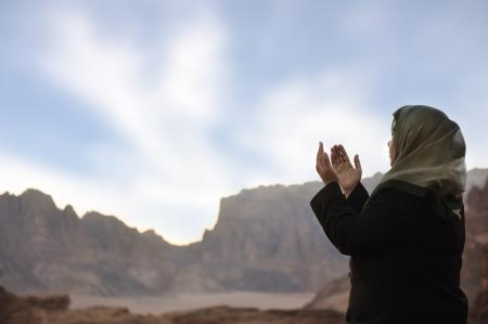 muslim prayer: silhouette of a muslim woman praying on the desert
